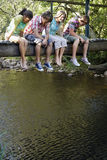 Подростки сидя на деревянном мосте смотря вниз на потоке Стоковая Фотография RF