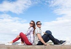 Подростки сидя спина к спине Стоковые Изображения