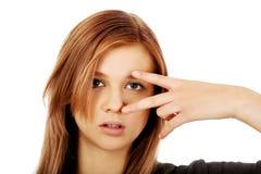 Подростковая женщина с знаком победы на глазе Стоковые Фото