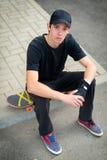 Подростковое усаживание скейтбордиста Стоковые Изображения RF
