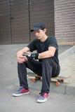 Подростковое усаживание скейтбордиста Стоковое Изображение RF