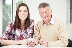 Подростковому деду внучки показывающ как использовать передвижной Phon стоковая фотография