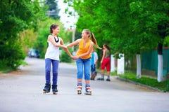 Подростковые девушки ролика катаясь на коньках на улице Стоковое Изображение