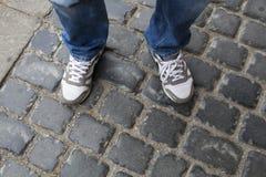 Подростковые ноги в тапках и голубых джинсах стоя на вымощая камнях Стоковые Изображения RF