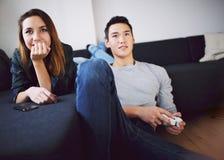 Подростковые пары наслаждаясь играющ видеоигру дома стоковое изображение rf