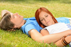 Подростковые пары ослабляя на глазах закрытых травой Стоковая Фотография RF