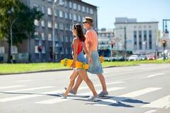 Подростковые пары с скейтбордами на crosswalk города Стоковые Изображения RF
