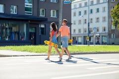 Подростковые пары с скейтбордами на crosswalk города Стоковое Изображение