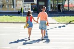 Подростковые пары с скейтбордами на crosswalk города Стоковое Изображение RF