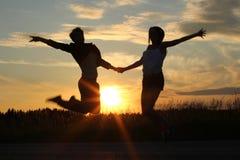 Подростковые сестры, делая тренировки на заходе солнца Стоковое фото RF
