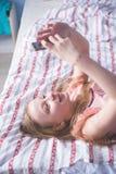 Подростковый лежать на ей назад кладет в постель и взгляды в телефоне Стоковые Фото