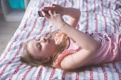 Подростковый лежать на ей назад кладет в постель и взгляды в телефоне Стоковые Изображения