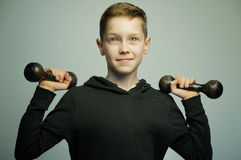 Подростковый мальчик спорта с гантелями и стильной стрижкой, съемкой студии Стоковая Фотография RF