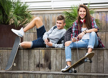 Подростковый ослаблять с мобильными телефонами Стоковая Фотография