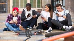 Подростковый ослаблять с мобильными телефонами Стоковые Изображения