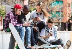 Подростковый ослаблять с мобильными телефонами Стоковое Изображение