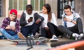 Подростковый ослаблять с мобильными телефонами Стоковые Фото