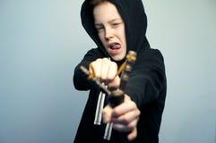 Подростковый плохой мальчик с рогаткой и стильной стрижкой, съемкой студии Стоковые Изображения RF