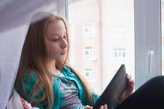 Подростковый сидит на окне и книге чтения в таблетке стоковое фото