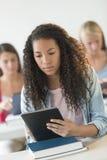 Подростковый студент используя таблетку цифров на столе стоковое изображение rf