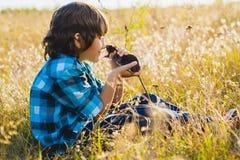 Подростковый счастливый мальчик играя с любимчиком крысы внешним стоковое изображение