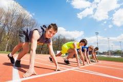 4 подростковых бегуна выровнялись вверх по готовому для того чтобы участвовать в гонке Стоковое Фото