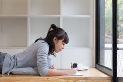 подросток азиатской девушки женский изучая на школе Студент лежа и Стоковая Фотография RF