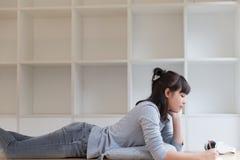подросток азиатской девушки женский изучая на школе Студент лежа и Стоковые Фотографии RF
