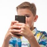Подросток в рубашке шотландки с телефоном в его руке Стоковое Изображение