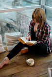 Подросток девушки сидя с книгой на балконе Стоковые Фото