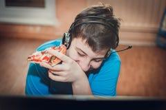 Подросток есть пиццу сидя на компьтер-книжке стоковое фото