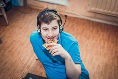 Подросток есть пиццу сидя на компьтер-книжке стоковое фото rf