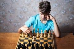 Подросток играя шахмат Стоковое Изображение