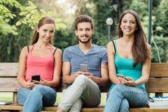Подросток на парке используя умные телефоны Стоковое фото RF