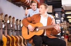 Подросток одобряет выбор гитары Стоковое фото RF