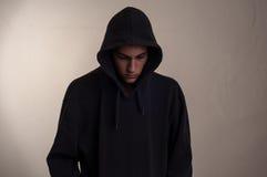 Подросток при hoodie смотря вниз Стоковое фото RF