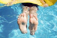 Подросток плавает на циновке в бассейне Стоковое фото RF