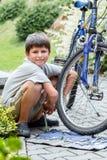 Подросток ремонтируя его велосипед, изменяя сломанная покрышка стоковое изображение