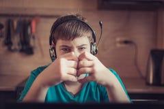 Подросток сидя на компьтер-книжке стоковая фотография rf