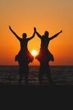 Подросток сидя на плечах друзей в заходе солнца Стоковые Изображения RF