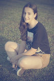 Подросток сидя на траве Стоковая Фотография RF