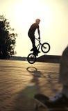 Подросток скачет на велосипед outdoors, мальчик на скейтборде, городском styl стоковые изображения rf