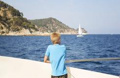 Подросток смотрит море от палубы шлюпки Стоковые Фото