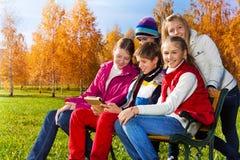 Подросток с устройством в парке Стоковые Фото