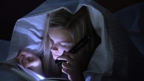 Подросток читая книгу с электрофонарем сток-видео