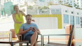 Подруга Гая ждать на террасе около бассейна используя smartphone река ландшафта kremlin города отраженное ночой сток-видео