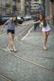 Подруга 2 жизнерадостных шла совместно через улицу Путешествия Стоковая Фотография RF