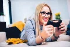 Подруга играя видеоигры с консолью и парнем Детали симпатичного современного образа жизни стоковое фото rf
