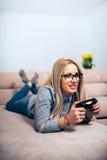 Подруга наслаждаясь видеоиграми и имея потеху в современном образе жизни стоковое фото rf