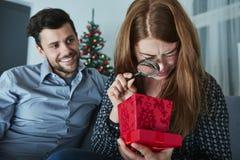 Подруга смотрит скептичной к ее подарку рождества стоковая фотография rf